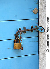 Padlock at Closed Old Blue Wooden Door