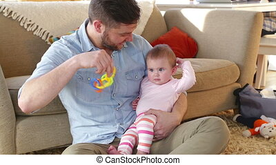 Father entertaining his daughter with her toys - Father...