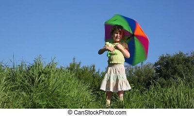 girl turns umbrella on meadow