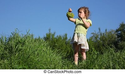 girl eating grapes on meadow
