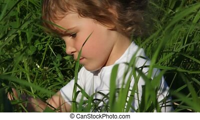 girl playing in grass and smiling