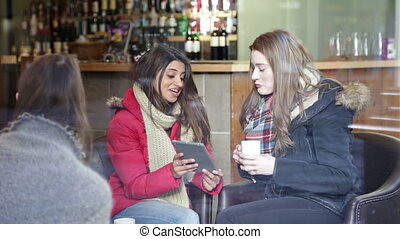 Two women using a digital tablet in a cafe