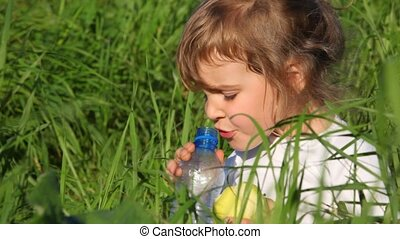 girl drinking water from  bottle close-up