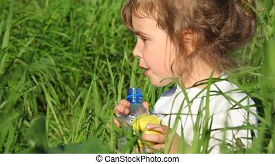 girl drinking water from bottle and eating apple