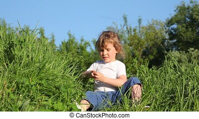 girl  picking up the grass and throwing it up