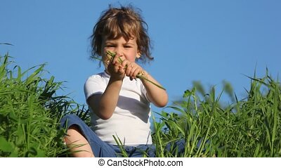 girl playing with grass and smiling