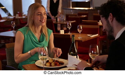 Young couple eating in a restaurant - Young man and woman...