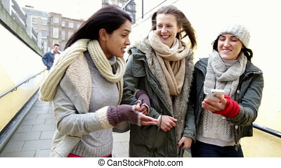 Three women looking at a smartphone as they walk together -...
