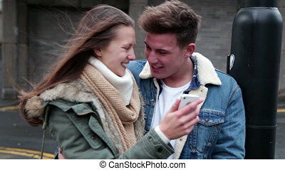Young couple looking at a smartphone together.