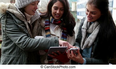 Three women on a city balcony using technology together -...