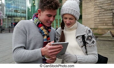 Two young adults using a tablet outdoors