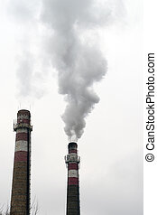 factory chimney with smoke - two brick smokestacks with...
