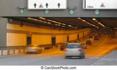 Cars move in tunnel, time lapse. Day.