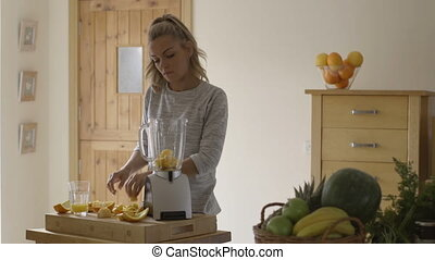 Making a smoothie - Young woman in her kitchen preparing a...