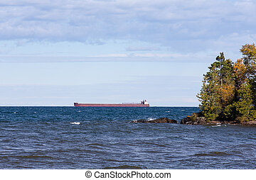 Great Lakes Freighter Passing Behind a Rocky Island - Great...