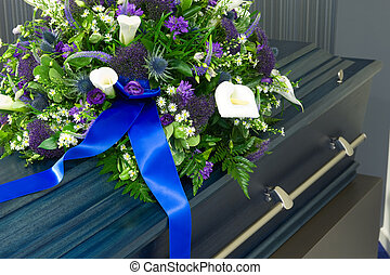 Coffin in morgue - A blue coffin in a morgue with a flower...