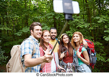 friends with backpack taking selfie by smartphone -...