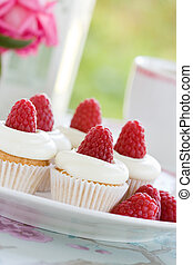 Afternoon tea - Mini cupcakes decorated with raspberries and...