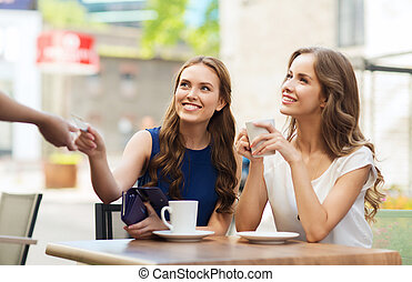 women with credit card paying for coffee at cafe - people,...