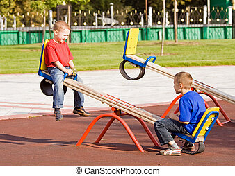Children on a seesaw - Boys playing on a seesaw on a...