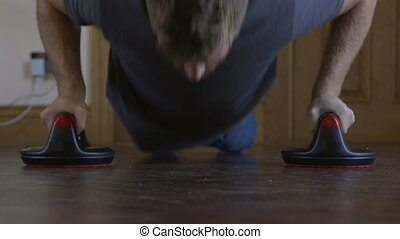 Doing press ups at home - Front facing view of a man doing...