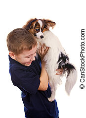 Boy and small dog - Boy bearing a puppy in his arms