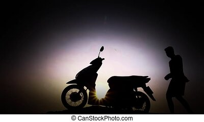 A man starts driving a motorcycle, silhouette