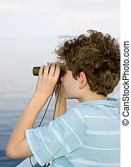 boy binoculars - one young messy haired boy looking over a...