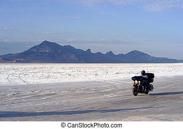 Motorcross - Biker driving across Bonneville Salt Flats,...