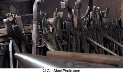 blacksmith tools in a workshop - Many used tools hung on a...