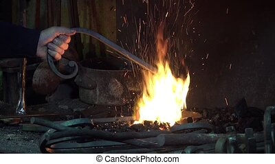 blacksmith artist in his workshop - forging scrolls with hot...