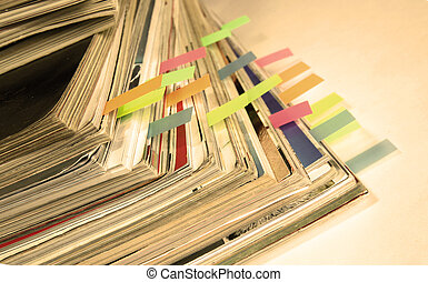 Dingy sepia-style photo of pile of old magazines with...
