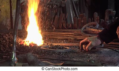 blacksmith artist in his workshop - functional heating the...