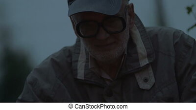 Aged man thinking and keeping an eye to the fire