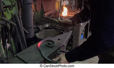 blacksmith artist in his workshop - planing a scoll