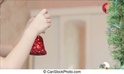 little girl hangs up the bell on the Christmas tree