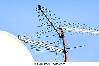 Satelite dish and tv antenna with the blue sky in the...