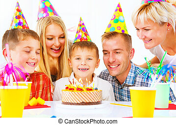 Birthday. Little boy blows out candles on birthday cake at party