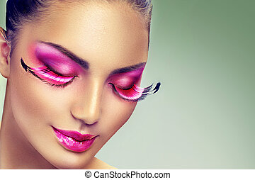 Creative holiday makeup with false long purple eyelashes...