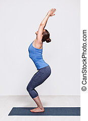Woman doing ashtanga vinyasa yoga asana Utkatasana - Sporty...