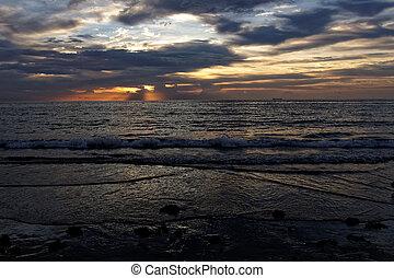 Sunrise Behind Clouds Over Ocean - Orange sun rising behind...