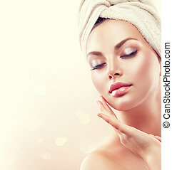 Spa woman. Beautiful girl after bath touching her face