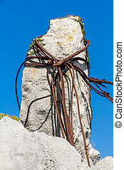 Rusty iron cables looped around limestone rock - Old rusty...