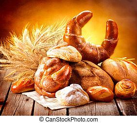 Various bread and sheaf of wheat ears on a wooden table