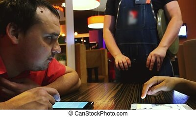 Business couple in a restaurant using a phone and waiting an...