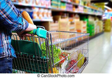 Man pushing shopping cart in the supermarket aisle - Man...