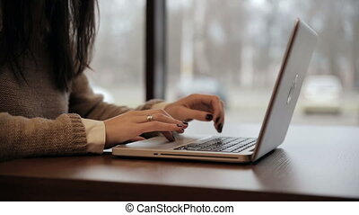 Businesswoman working on laptop in cafe. static