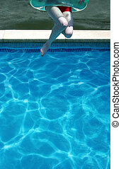 Young woman jumping in swimming pool - Young woman jumps...