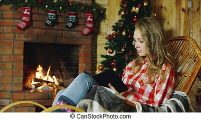 Woman reading electronic book near the fireplace