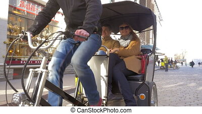 Couple riding in bicycle taxi and talking to each other -...